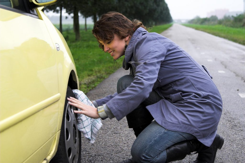 woman is changing her tire