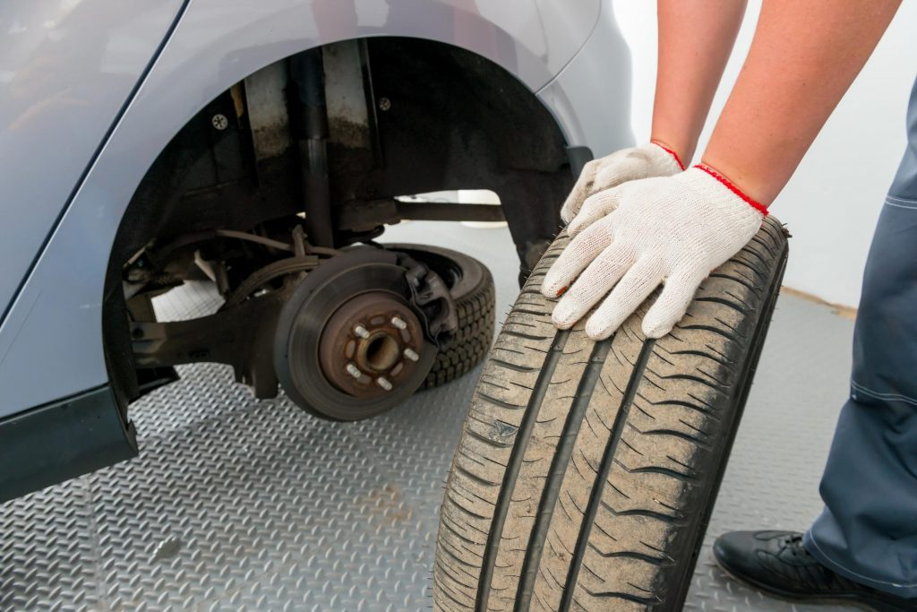 car worker is helping to change flat tires