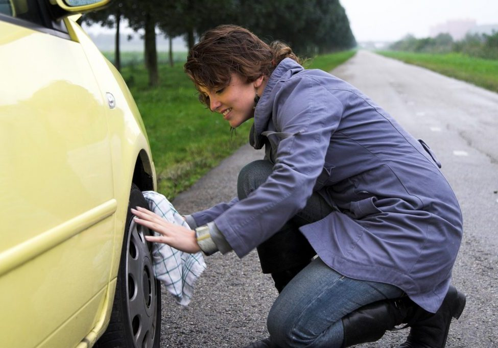 woman is getting her tire changed